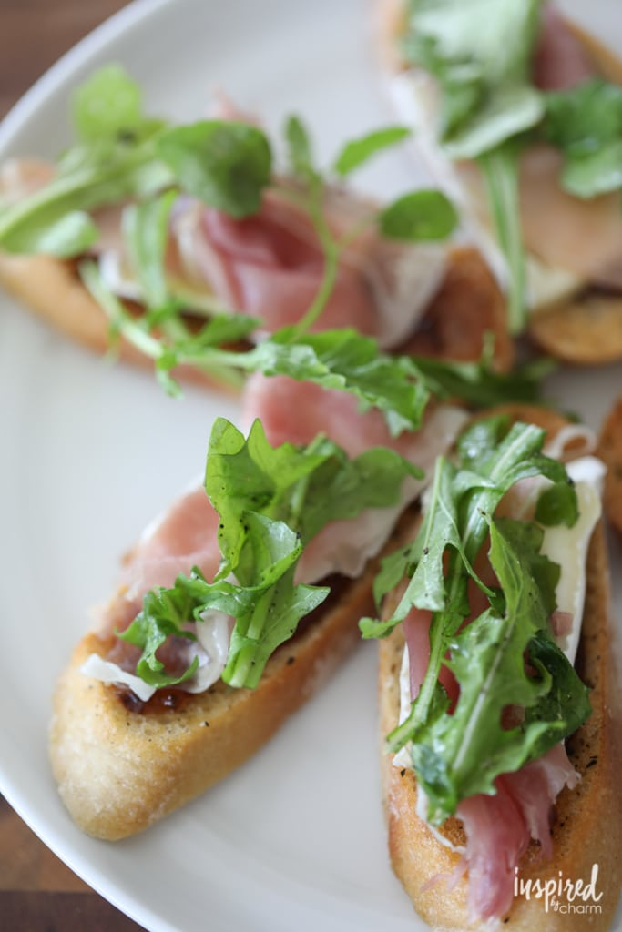 This Brie, Fig, and Prosciutto Crostini recipe makes a flavorful and easy appetizer. #appetizer #crostini #fig #arugula #brie #prosciutto